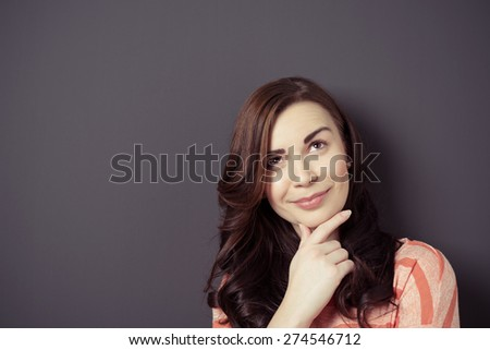 Close up Smiling Thoughtful Young Woman with Hand on her Chin Leaning Against Gray Wall, Emphasizing Copy Space, While Looking Up. - stock photo