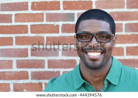 Close up Smiling Young Black Man Wearing Eyeglasses, Looking at the Camera Against Brick Wall Background with Copy Space - stock photo