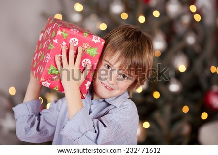 Close up Smiling Young Male Kid Carrying Red Christmas Box at his Shoulder While Looking at the Camera. Captured Indoor with Lighted Christmas Tree at the Background. - stock photo