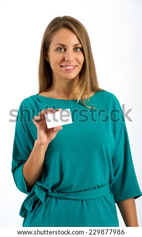 Close up Smiling Young Pretty Woman in Elegant Blue Green Clothes, Showing Small White Empty Card While Looking at the Camera. Isolated on White Background.