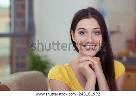 Close up Smiling Young Woman with Long Hair, Wearing Yellow Shirt, Putting her Both Hands Under the Chin While Looking at the Camera. - stock photo