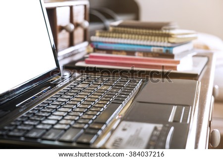 Close-up, soft focus keyboard with pile of books, selective focus, shallow depth of field - stock photo