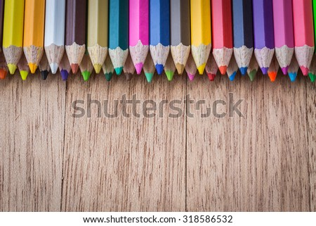 Close up stack colour pencils on wooden background - stock photo