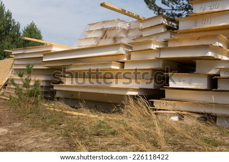 Close up Stacked of Building Materials Ready for Real Estate House Construction Piled on Grassy Landscape at the Project Site. - stock photo