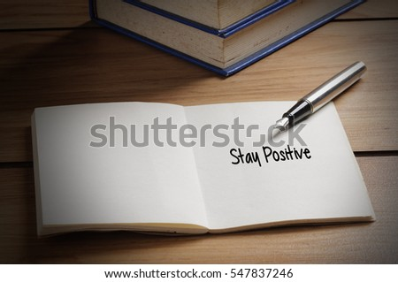 Close up stay positive word written on book