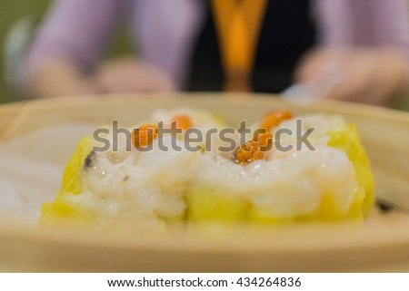 Close up steamed shrimp dumplings dim sum with girl in the background - stock photo