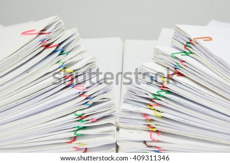 Close up step pile overload document of receipt and report with colorful paperclip on white table.