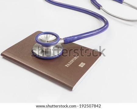 Close up stethoscope and passport on white background - stock photo