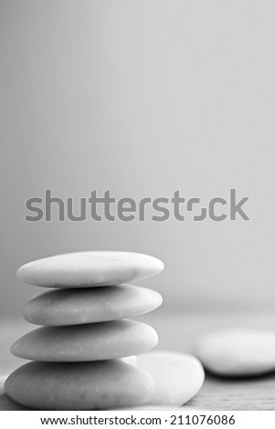 Close up still life black and white view of a stack of natural white stones piled on top of each other in balance against a plain background. Neutral, calm and relaxing health spa interior colors.
