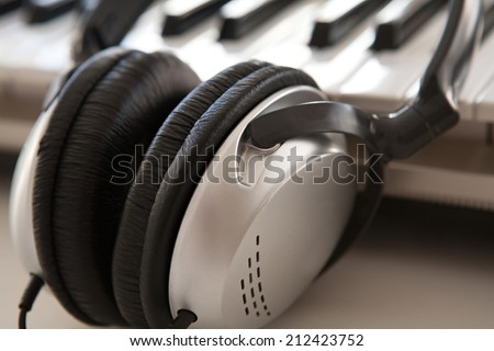 Close up still life detail of a pair of professional headphones and an electric keyboard laying together on a dj desk. Music and technology equipment objects, interior. - stock photo