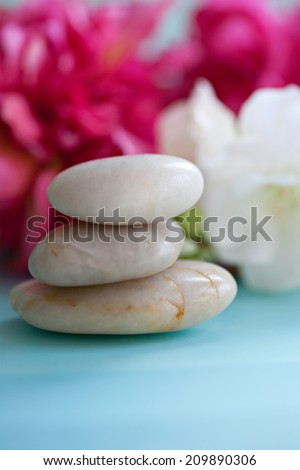 Close up still life detail of a pile of natural smooth white stones balancing in a stack against bright pink blossom flowers in a blue health spa background, interior. Nature objects and zen energy. - stock photo