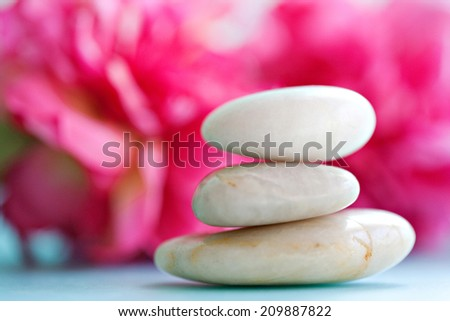 Close up still life detail view of a pile of natural smooth white stones balancing in a stack against bright pink blossom flowers in a health spa background, interior. Nature objects and zen energy. - stock photo