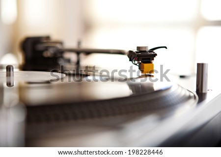 Close up still life detail view of a record player playing music with the needle touching the groove of the album against a sunny golden window in a music club interior. DJ equipment working in venue. - stock photo