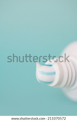Close up still life detail view of refreshing stripy toothpaste pouring out of a tooth paste tube isolated on a spacious clean blue background, home interior. - stock photo