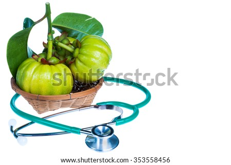 Close up still life garcinia atroviridis fresh fruit on wood basket and stethoscope on white background. Herb sour flavor lots of vitamin C for good health. Free form copy space. - stock photo