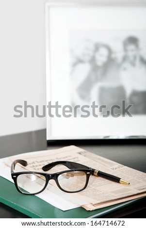 Close up still life of a pair of reading glasses and a black pen laying on an orange financial newspaper on a dark wooden writing desk with a family photo frame. Office interior with no people. - stock photo