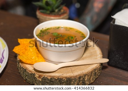 Close Up Still Life of Hot Bowl of Garnished Soup in Styrofoam Bowl with Plastic Spoon Served on Wooden Tree Trunk Round with Tortilla Chips