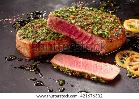 Close Up Still Life of Seared Tuna Steaks Topped with Fresh Pesto on Dark Gray Surface Dirtied with Oil and Lemon Slices - stock photo