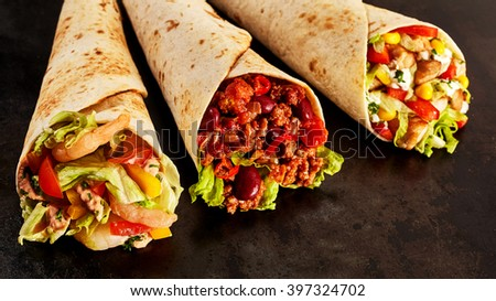 Close Up Still Life Trio of Tex Mex Fajita Wraps on Dark Background - Variety of Gourmet Grilled Flour Wraps Stuffed with Shrimp, Chili and Chicken and Fresh Vegetables - with Copy Space - stock photo