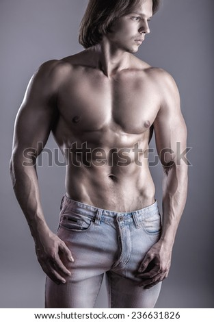 Close-up strong athletic man on a gray background - stock photo