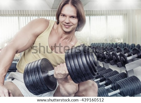 Close up strong man at the gym lifting weights - stock photo