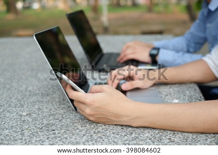 close up student playing smartphone device and working at notebook laptop:two man sitting at park outdoor campus and relaxing after class:education concept. - stock photo