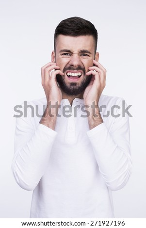 Close-up studio portrait of a furious shouting man irritable itchy his beard. Isolated on a light background. - stock photo