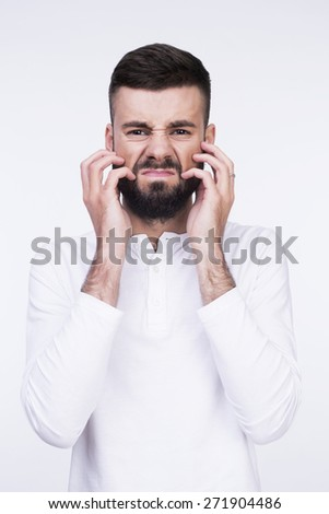 Close-up studio portrait of an angry man irritable itchy his beard. Isolated on a light background. - stock photo