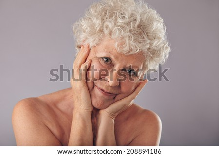 Close-up studio portrait of attractive senior woman with her head resting in her hands against grey background. Happy old woman with hands on face looking at camera. - stock photo