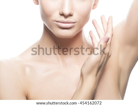 Close-up studio portrait of beautiful young caucasian brunette woman with natural lips and make-up isolated on white. Naked shoulders. Touch her perfect skin. - stock photo