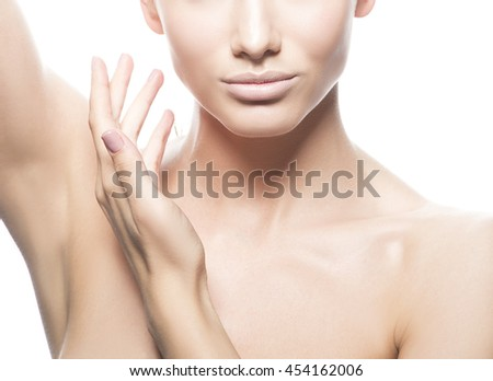 Close-up studio portrait of beautiful young caucasian brunette woman with natural lips, make-up and blue eyes isolated on white. Touch her perfect skin. Studio portrait.  - stock photo