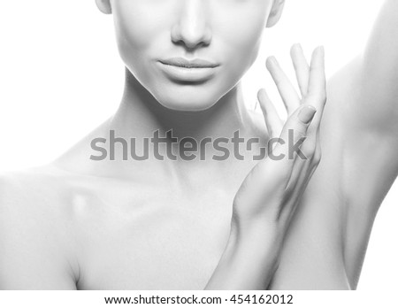 Close-up studio portrait of beautiful young caucasian brunette woman with natural lips, make-up and blue eyes isolated on white. Touch her perfect skin. Studio portrait. Black and white - stock photo