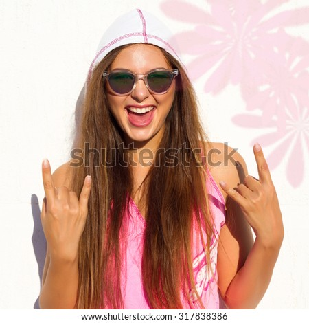 Close up studio portrait of cheerful brunette hipster girl going crazy making funny face and showing her tongue.Laughing portrait,crazy mood. White urban wall background. - stock photo