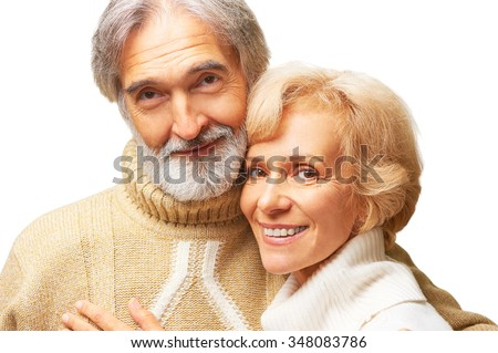 Close up studio portrait of happy elderly couple wearing sweaters embracing, isolated on white - stock photo