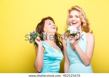 Close up studio portrait of two best friends pretty young blonde girls posing in studio on yellow background, a small bouquet of flowers. Bright colors.