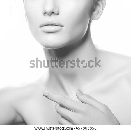 Close-up studio portrait of young caucasian brunette woman with natural lips, make-up and blue eyes isolated on white. Touch her perfect skin. Studio portrait. Black and white - stock photo