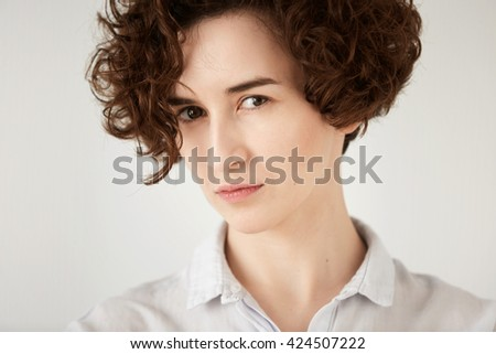 Close up studio portrait of young displeased or angry woman looking in annoyance. Isolated headshot of irritated girl with short curly red hair white hipster shirt. Human face expressions and emotions - stock photo