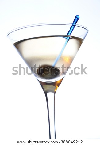 Close-up studio shot of a Dry Martini cocktail garnished with olive, on white background. - stock photo