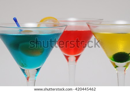 Close-up studio shot of a group of three garnished Martini cocktails (red, blue and yellow) on white (grey) background. - stock photo