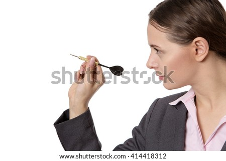 Close up studio shot of a young, pretty business woman,  aiming a dart, ready to throw.  - stock photo