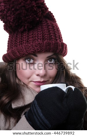 Close up studio shot of a young, pretty model, wearing an woollen winter hat, coat and gloves,whilst holding a mug.