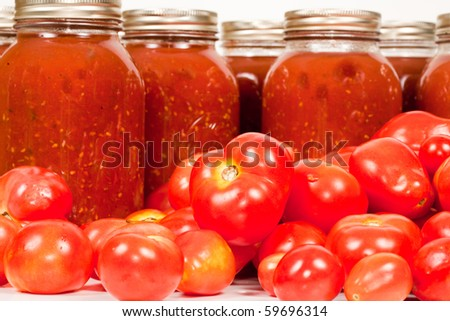 Close up studio shot of some organic field tomatoes with mason jars filled with freshly homemade tomato sauce. - stock photo