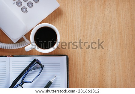 Close up Stuffs on Wooden Table of a Businessman with A Cup of Pure Black Coffee, Notes and Pen, Eye Wear and Telephone at the Office - stock photo