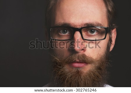 Close up stylish gorgeous young  businessman with long beard s on black background