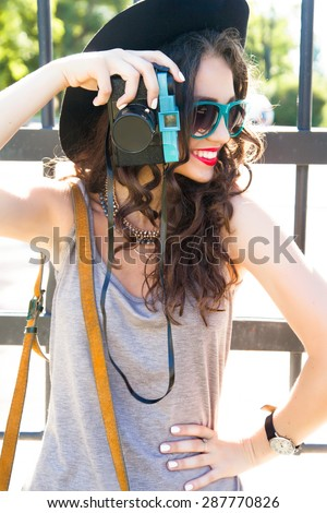 Close-up stylish portrait of young girl make picture and  posing on the street on stylish outfit,wear summer glamour sunglasses,summer light long dress,small bag and big  black hat.Look at camera - stock photo