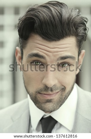 Close-up stylized portrait of a handsome young businessman in suit with playful fun expression - stock photo