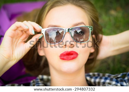 Close up summer bright portrait of young woman with red lips and blond hair.  Relaxing after work,laying on the grass in the city park. Wearing casual checkered blue shirt and stylish sunglasses. - stock photo