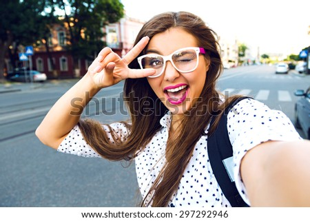 Close up sunny portrait of young happy pretty girl making selfie and smile, wearing cute hipster clear glasses, lovely emotions, long brunette hairs, perfect ski, bright make up. - stock photo