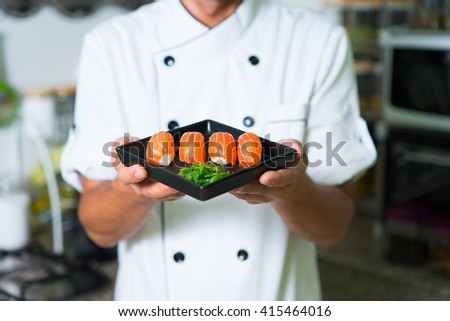 Close up Sushi in chefs hands. Focus on sushi - stock photo
