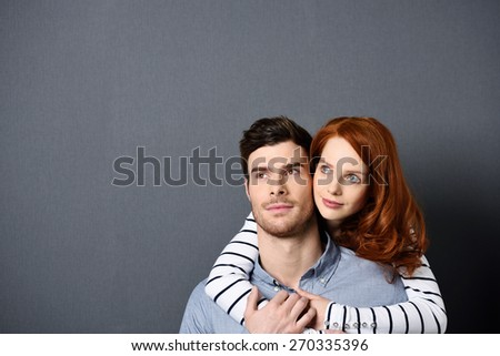 Close up Sweet Lovers - Pretty Woman Hugging her Handsome Man While Looking Upper Left of the Frame. Isolated on Gray with Texts Space. - stock photo